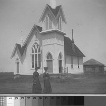 Abigail Fulkerth and an unidentified woman stand before Turlock's first church, circa ...