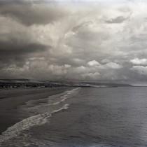 Beach scene with harbor entrance in background, Newport Beach, California: Photograph