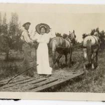 Man and woman riding a hay sled pulled by horses