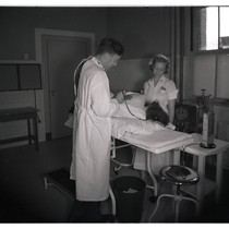 Doctor and nurse performing exam on chest clinic patient at San Francisco ...