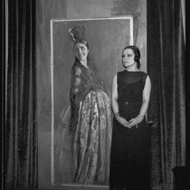 Artist Maroussia Valero standing next to her painting of a spanish woman, ...