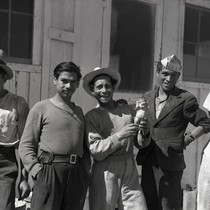 Five Mexican workers in front of camp building, one worker holding a ...