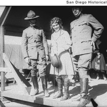 Actress Mary Pickford standing with two army officers on a covered wooden ...