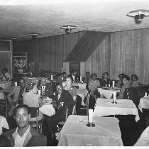 Male and female patrons seated at white cloth covered tables, Slim Jenkins ...
