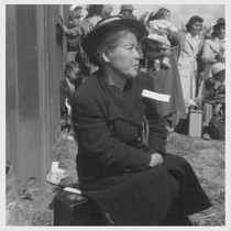 This farm mother of Japanese ancestry is awaiting the evacuation buses which ...