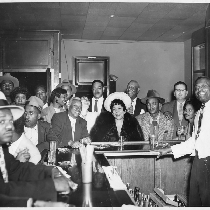 Group photograph of patrons seated around bar at Slim Jenkins Bar and ...