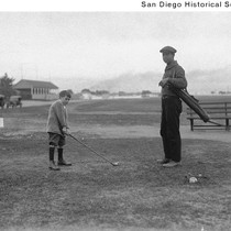 A small boy playing golf with an adult holding the golf bag