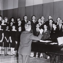 Photograph of a choral group with Lee Kjelson, Associate Professor of Music