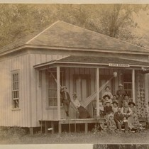 [Group portrait in front of Long Branch cabin]