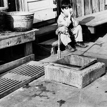 Child on porch with basins