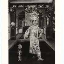 Actor as gallant warrior in long embroidered civilian gown and ornate headdress ...