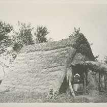 [A-frame house with grass roof.]