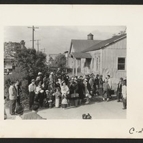 Farm families of Japanese ancestry awaiting the evacuation buses which will take ...