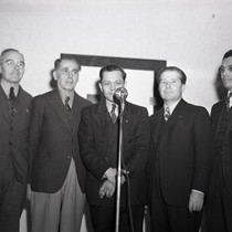 Five men standing in front of a microphone