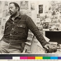 Eldridge Cleaver in front of press clippings on wall of room in ...