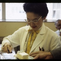 Asian woman in white lab coat serving cake