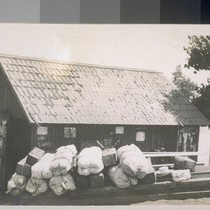 [Bedrolls and belongings of Japanese laborers stacked outside unidentified building in Ryde, ...