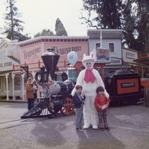 Easter Bunny poses with two children in front of Frontier Village Railroad