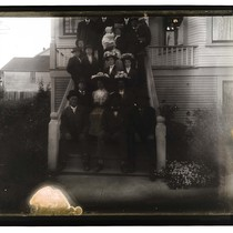 [About twenty people posing on the steps of a house]