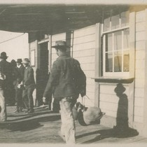 """Blanket Stiff"". [Men carrying bedrolls and belongings in front of unidentified building.]"