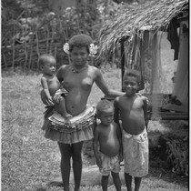 Adolescent girl wearing short fiber skirt, with other younger children