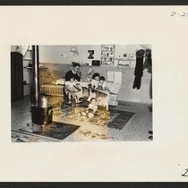 An evacuee family spends a quiet evening in their barracks. The decoration ...