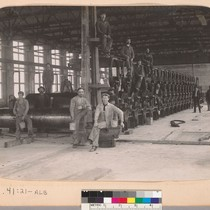 [Men standing by and sitting on machinery at a mill.]
