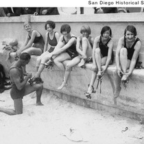 Women in bathing suits putting on roller skates, one receiving assistance from ...