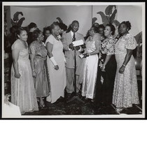 B.F. McLaurin standing at microphone handing envelope to group of women