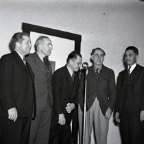 Five men standing in front of a microphone, one man bowing