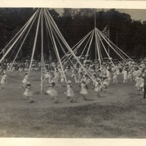 Children weave streamers around a may pole during the second annual May ...