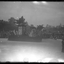 1928 Rose Parade spectators watching Sherman Institute's float depicting scenes of American ...