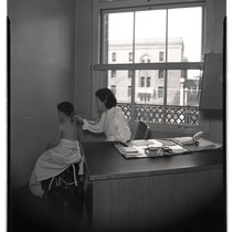 Clinician using stethoscope on pediatric chest clinic patient at San Francisco General ...