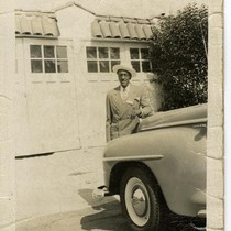 African American man in driveway, leaning against car