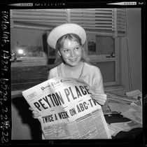 17 year old Mia Farrow holding Peyton Place newspaper as she waits ...