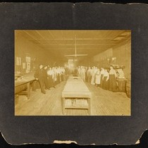 About thirty persons inside a manufacturing plant, cabinet photograph, circa 1900s