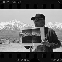 Japanese American man displays book of Ansel Adams' Manzanar photographs