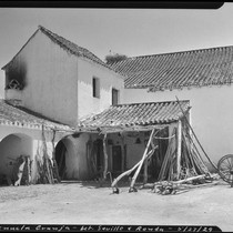 Agricultural equipment leaning against a roof, La Penucla Granja, Spain, 1929