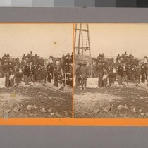 [Crowd of men, boys, and wagons near a tall wooden structure. Possibly ...