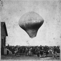 An early hot air balloon rises over a crowd during the first ...