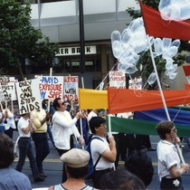 People marching in Lesbian and Gay Freedom Day parade with AIDS-related signs