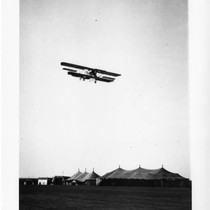 Aviator Martin in Martin Curtiss-type biplane in flight over tents (2)
