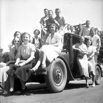 [16 students posed on an old car]