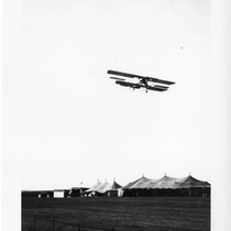Aviator Martin in Martin Curtiss-type biplane in flight over tents (3)