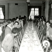 Dining hall with long tables and newly arrived Mexican workers standing at ...