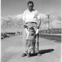 Manzanar, Calif.--Grandfather of Japanese ancestry teaching his little grandson to walk at ...