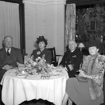 Admiral Hooper seated with a group of people at a table