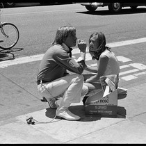 Couple sitting on sidewalk with bells on, Haight-Ashbury 1967