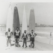 Alex Hokamp, Harry Mayo, Fred Hunt standing with surfboards at Cowell Beach