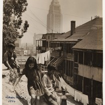 Three children playing behind houses in Boyle Heights